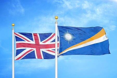 United Kingdom and Marshall Islands two flags on flagpoles and blue cloudy sky background Фото со стока