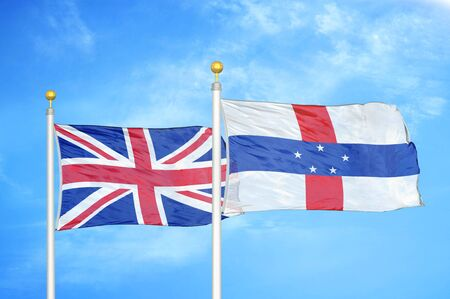 United Kingdom and Netherlands Antilles two flags on flagpoles and blue cloudy sky background