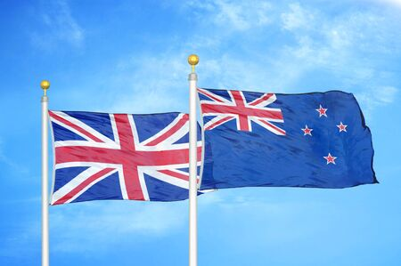 United Kingdom and New Zealand two flags on flagpoles and blue cloudy sky background