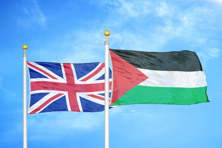 United Kingdom and Palestine two flags on flagpoles and blue cloudy sky background