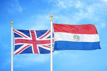 United Kingdom and Paraguay two flags on flagpoles and blue cloudy sky background