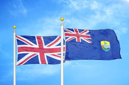 United Kingdom and Saint Helena two flags on flagpoles and blue cloudy sky background