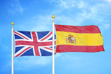 United Kingdom and Spain two flags on flagpoles and blue cloudy sky background