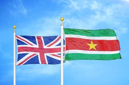 United Kingdom and Suriname two flags on flagpoles and blue cloudy sky background Фото со стока