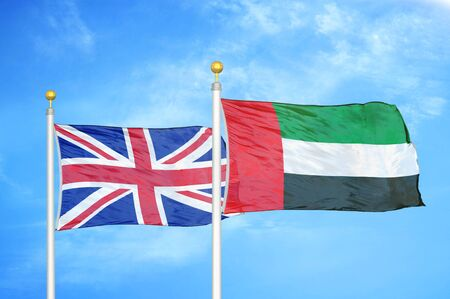 United Kingdom and United Arab Emirates two flags on flagpoles and blue cloudy sky background