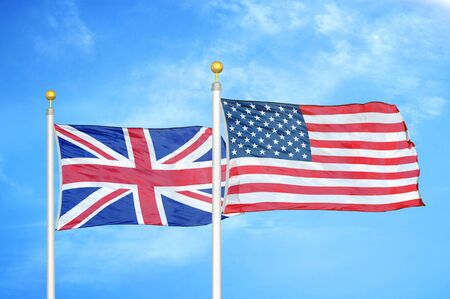 United Kingdom and United States two flags on flagpoles and blue cloudy sky background