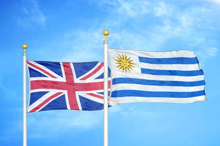 United Kingdom and Uruguay two flags on flagpoles and blue cloudy sky background