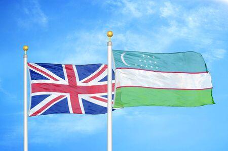 United Kingdom and Uzbekistan two flags on flagpoles and blue cloudy sky background Фото со стока