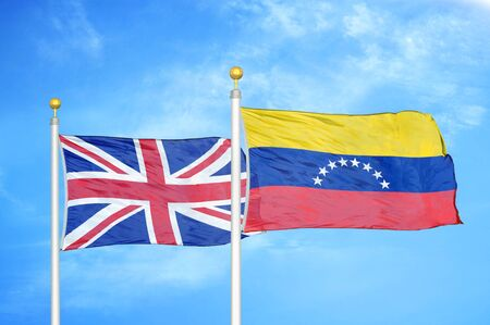 United Kingdom and Venezuela two flags on flagpoles and blue cloudy sky background Фото со стока