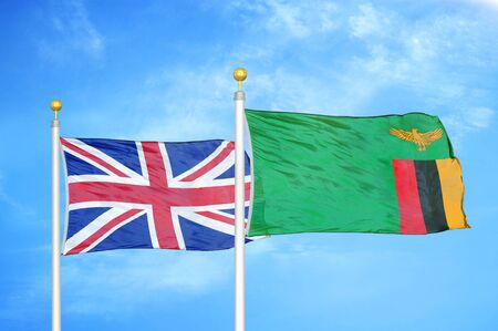 United Kingdom and Zambia two flags on flagpoles and blue cloudy sky background