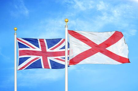 United Kingdom and Northern Ireland two flags on flagpoles and blue cloudy sky background Фото со стока