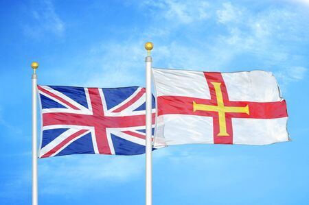 United Kingdom and Guernsey two flags on flagpoles and blue cloudy sky background Фото со стока