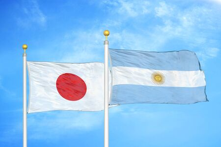 Japan and Argentina two flags on flagpoles and blue cloudy sky background Фото со стока
