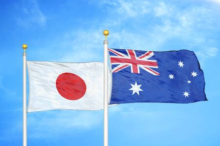 Japan and Australia two flags on flagpoles and blue cloudy sky background