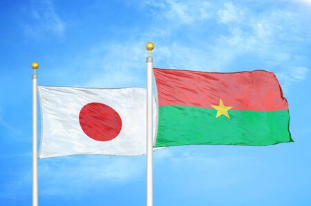 Japan and Burkina Faso  two flags on flagpoles and blue cloudy sky background