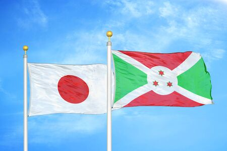 Japan and Burundi  two flags on flagpoles and blue cloudy sky background Фото со стока