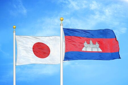 Japan and Cambodia  two flags on flagpoles and blue cloudy sky background