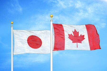 Japan and Canada two flags on flagpoles and blue cloudy sky background Stock Photo