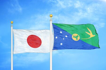 Japan and Christmas Island two flags on flagpoles and blue cloudy sky background Фото со стока