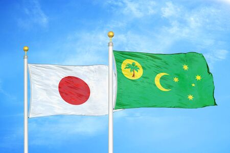 Japan and Cocos Keeling Islands two flags on flagpoles and blue cloudy sky background Фото со стока