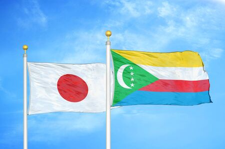 Japan and Comoros  two flags on flagpoles and blue cloudy sky background Фото со стока