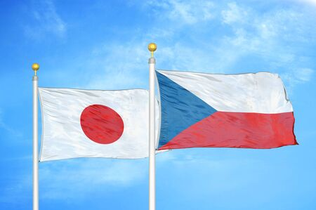 Japan and Czech Republic two flags on flagpoles and blue cloudy sky background Фото со стока