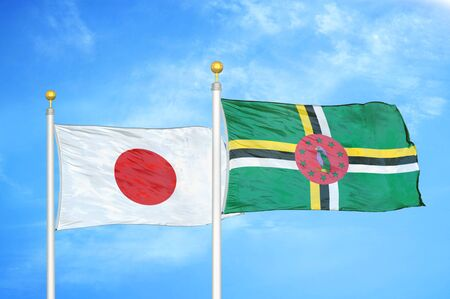 Japan and Dominica two flags on flagpoles and blue cloudy sky background