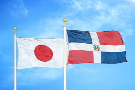Japan and Dominican Republic two flags on flagpoles and blue cloudy sky background Фото со стока