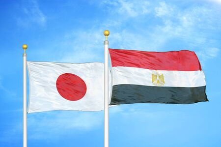 Japan and Egypt two flags on flagpoles and blue cloudy sky background