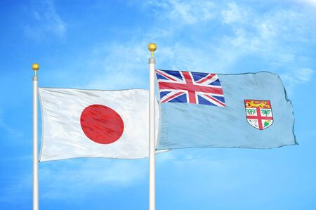 Japan and Fiji two flags on flagpoles and blue cloudy sky background Фото со стока