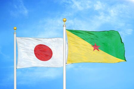 Japan and French Guiana two flags on flagpoles and blue cloudy sky background Фото со стока