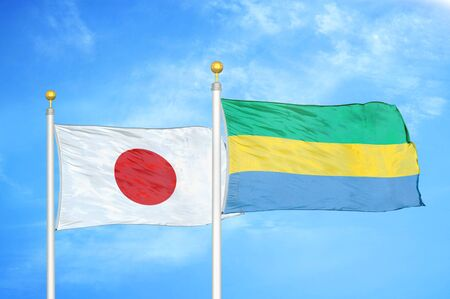 Japan and Gabon two flags on flagpoles and blue cloudy sky background Фото со стока