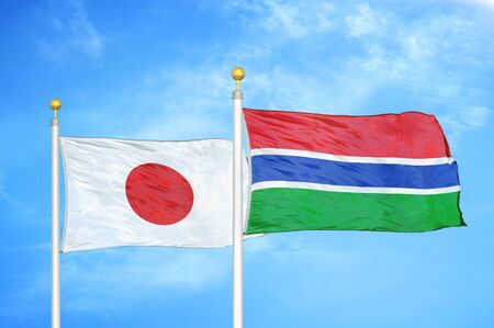 Japan and Gambia two flags on flagpoles and blue cloudy sky background Фото со стока