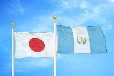 Japan and Guatemala two flags on flagpoles and blue cloudy sky background