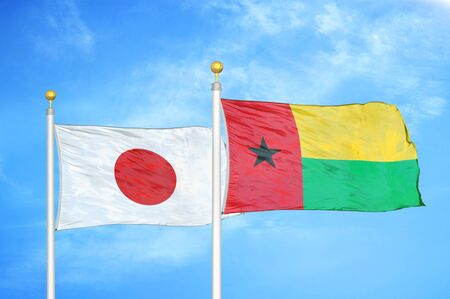 Japan and Guinea-Bissau two flags on flagpoles and blue cloudy sky background Фото со стока