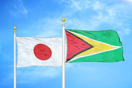 Japan and Guyana two flags on flagpoles and blue cloudy sky background