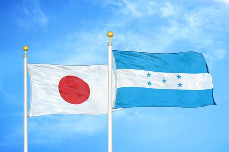 Japan and Honduras two flags on flagpoles and blue cloudy sky background Фото со стока