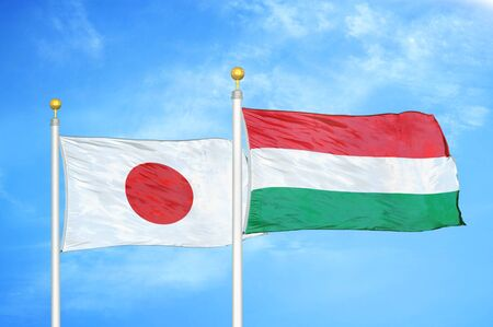 Japan and Hungary two flags on flagpoles and blue cloudy sky background Фото со стока