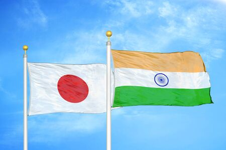 Japan and India two flags on flagpoles and blue cloudy sky background