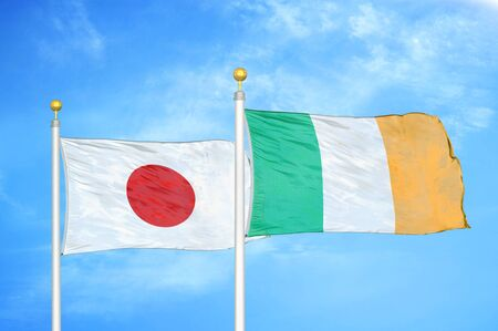 Japan and Ireland two flags on flagpoles and blue cloudy sky background Фото со стока