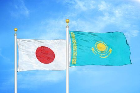 Japan and Kazakhstan two flags on flagpoles and blue cloudy sky background Фото со стока