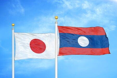 Japan and Laos  two flags on flagpoles and blue cloudy sky background