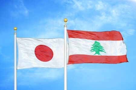 Japan and Lebanon two flags on flagpoles and blue cloudy sky background