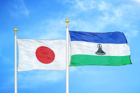 Japan and Lesotho two flags on flagpoles and blue cloudy sky background 스톡 콘텐츠
