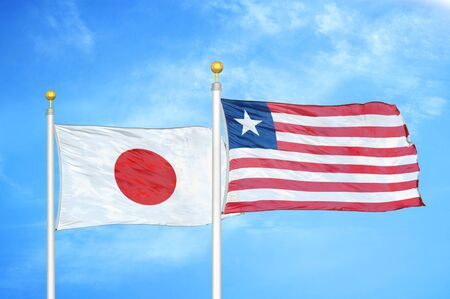 Japan and Liberia two flags on flagpoles and blue cloudy sky background