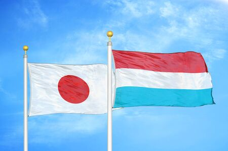 Japan and Luxembourg two flags on flagpoles and blue cloudy sky background