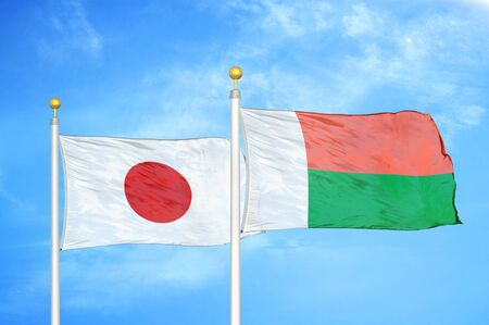 Japan and Madagascar two flags on flagpoles and blue cloudy sky background