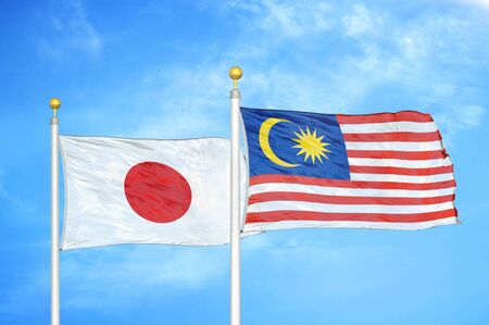 Japan and Malaysia two flags on flagpoles and blue cloudy sky background