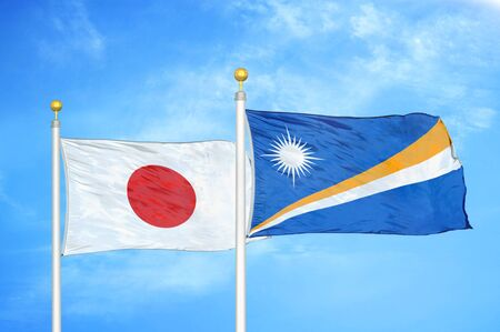 Japan and Marshall Islands two flags on flagpoles and blue cloudy sky background