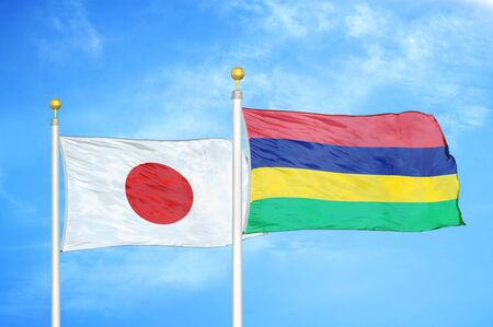 Japan and Mauritius two flags on flagpoles and blue cloudy sky background 스톡 콘텐츠